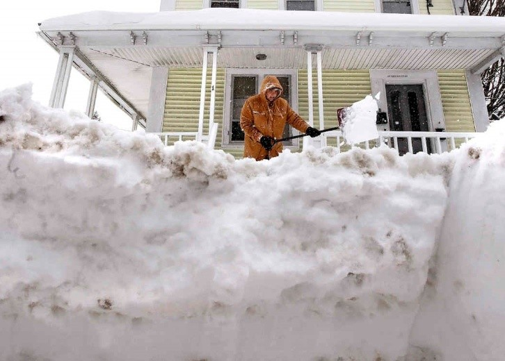 Ryan Jussif - Ryan Jussif shovels out a front porch and walkway in Derry, N.H., Monday, Feb. 13, 2017. Another winter blast of snow and strong winds moved into the Northeast on Sunday to the delight of some and the consternation of others, just days after the biggest storm of the season dumped up to 19 inches of snow in the region. (AP Photo/Charles Krupa)